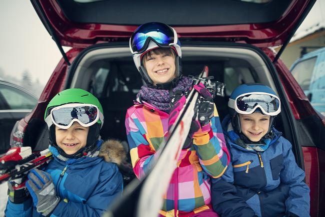 Famiglia con gli sci arriva in montagna in auto